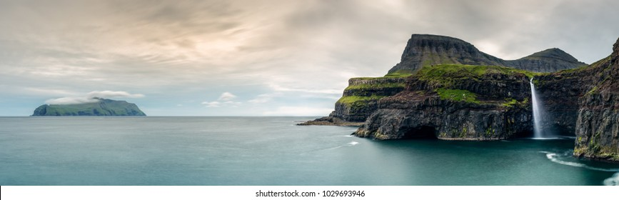 The Ga�sadalur waterfall in the Faroe Islands flows over a cliff to the ocean below. The Island of Mykines sits in the background with the early sunset like illuminating the clouds.