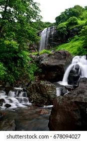 Waterfall flowing around rocks and green vegetation.