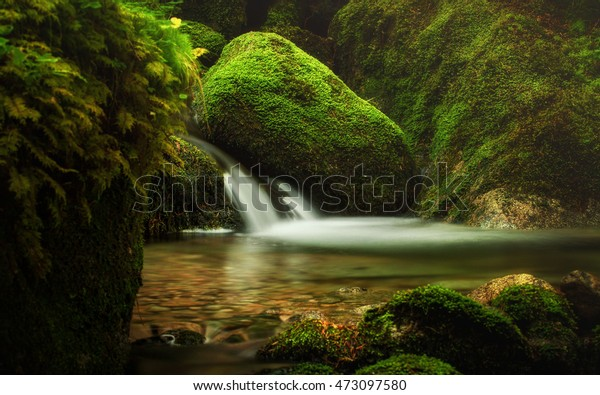Waterfall flowing between large rocks in a deep green forest - Slovak Republic.