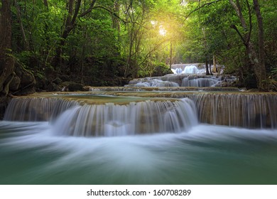 Waterfall flowing over rocks through lush green forest