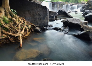 The waterfall is flowing through the rocks which has the root of tree on side. At Tat Ton National Park, Chaiyaphum, Thailand.