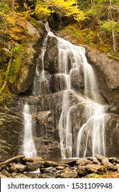 a waterfall flows in a beautiful fall location in the mountains with fall or autumn colors