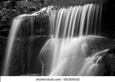 Waterfall in forest landscape long exposure flowing through trees and over rocks in black and white