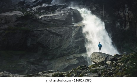Waterfall in forest, natural background. Krimml Waterfalls in High Tauern National Park (Austria). A man at a stone in front of a waterfall