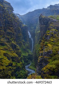 The waterfall Glymur, with a fall of 196 m., is the second highest waterfall of Iceland. In the background, standing right on the edge of a steep cliff, two people are looking out over the ravine.