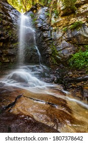 Waterfall hidden deep in a mountain ravine