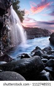 Waterfall into the Pacific Ocean at sunset, near Queen's Bath, Kauai, Hawaii