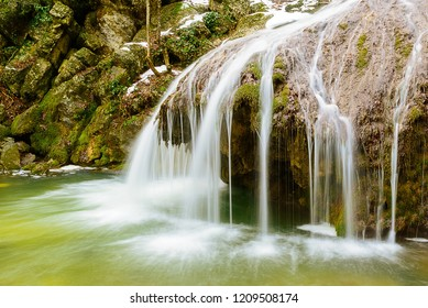 Waterfall Jur-Jur in winter, green moss and water, Crimea, Russia. White streams of water falling from a large stone in the forest, green moss around, green water
