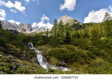 Waterfall at lake Seebensee with forest and mountain range in the background - Trail from Ehrwalder Alm to Coburger Hut in the Zugspitze area, Tyrol, Austria