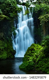 Waterfall landscape. Focus on waterfall, blurred leaves. Beautiful waterfall in tropical rainforest. Jungle river. Adventure in Asia. Cemara waterfall in Bali. Slow shutter speed, motion photography.