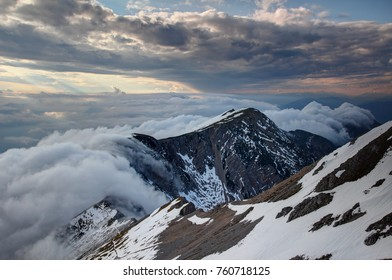 Waterfall like low level orographic clouds flowing down the steep north face of Karavanke Karawanken ridge with snow patches at sunset, Stol Hochstuhl peak Kranjska Slovenia Carinthia Austria Europe