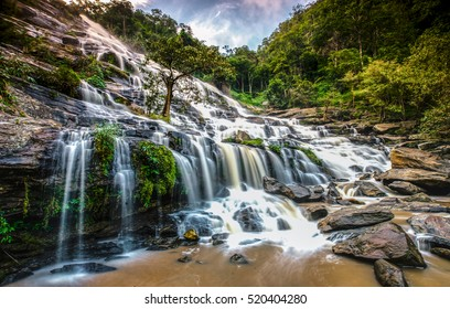 waterfall in mountain forest under great sky.