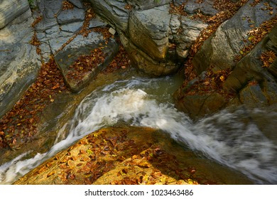 Waterfall in Mountains. Landscape mountain river in autumn forest at sunlight. Fast jet of water at slow shutter speeds give a beautiful magic effect.