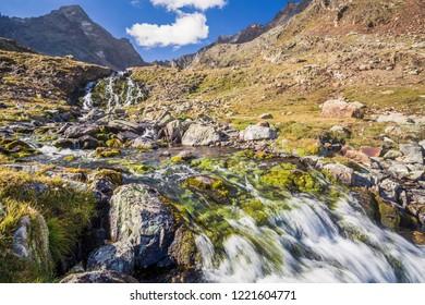 Waterfall near alpine lake, Lac long, Valpelline, Aosta Valley, Bionaz, Italy