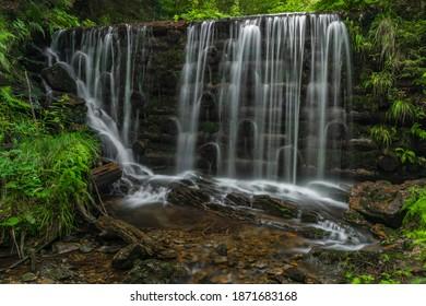 Waterfall near Kouty nad Desnou village in summer day in forest - Shutterstock ID 1871683168