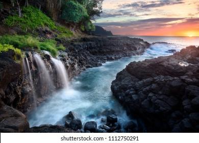 Waterfall near Queen's Bath at sunset, Kauai, Hawaii
