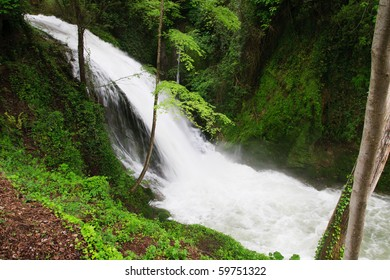 Waterfall on rapid river surrounded with green vegetation