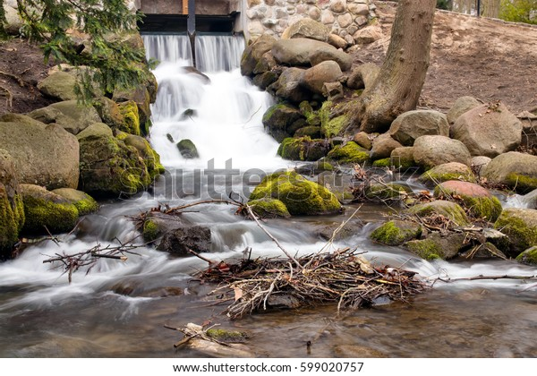 Waterfall on a small river in a park. Moss on a rocks. Tranquil scene.