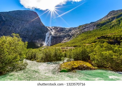 Waterfall, river and green trees on the way to Briksdal or Briksdalsbreen glacier in Olden, Norway