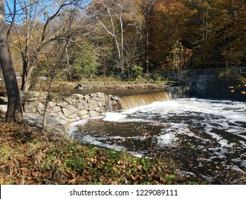 waterfall with rocks on river with trees and leaves