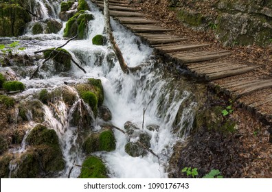 Waterfall running under a narrow wooden path at Plitvice Lakes National Park in Croatia