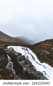 Waterfall in Scotland on a foggy moody day with mountains in the background