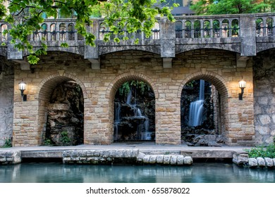 Waterfall seen through an old historic bridge alongside the River walk in San Antonio Texas (long exposure for silky water effect)