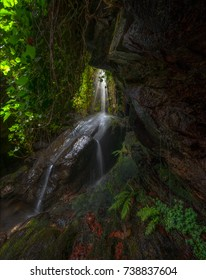 Waterfall seen through the opening of a cave