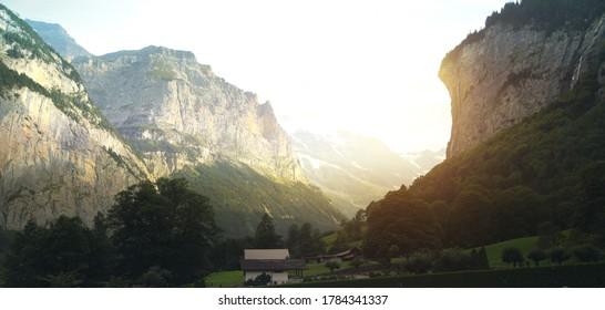 Waterfall and small house in Jungfrau valley in Lauterbrunnen, Switzerland. - Shutterstock ID 1784341337