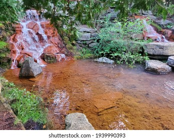 Waterfall and still water over small orange rocks under trees in the park. white, red, orange, rocks, trees, waterfall.