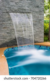 Waterfall stone in house near swimming pool at luxury modern house in Thailand.