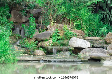 Waterfall and stones with green trees in the garden.