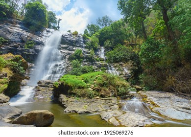 The waterfall is surrounded by beautiful trees and rocks.
