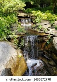 Waterfall trickling over rocks in ornamental garden