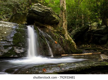 Waterfall under boulder in forest