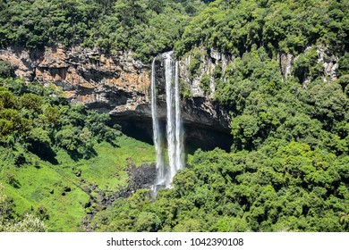 Waterfall under green forest and rock