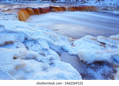 Waterfall under the ice in winter frost. Winter landscape