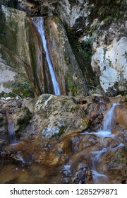 Waterfall with very cold water in a warm winter forest in the depths of the Italian mountains. Each pebble has its own soul, history.