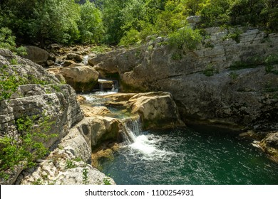 a waterfall and its wild green water in gorges of southern France