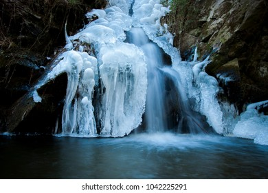Waterfall in winter with ice in nature. Waterfall in the Czech Republic,