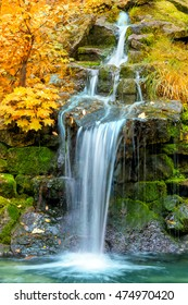 Waterfall in yellow Autumn forest, landscape, vertical