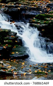 Waterfalls Among Rocks in the Forest During Fall Foliage