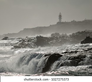 Waterfalls in the coast and lighthouse in background, La Garita, Gran canaria