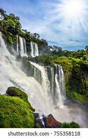 Waterfalls Iguazu, Argentina. The tropical sun illuminates the seething waters. Picturesque basaltic ledges form the famous waterfalls. The concept of active and exotic tourism