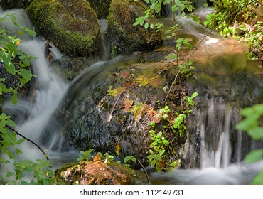 Waterfalls over rocks at the first hint of Autumn