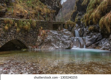 Waterfalls of Val Vertova on a winter morning, the water appears still in the natural landscape, horizontal image of mountain landscape with waterfall