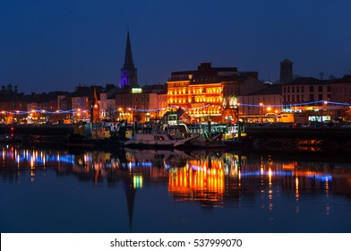 Waterford, Ireland. Panoramic view of a cityscape at night with illumination in Waterford, Ireland. It is the oldest city in the country where located many restaurants, shops, bars. Moored ship