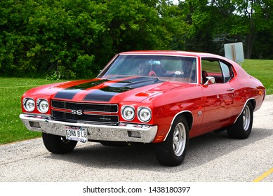 Waterford, Wisconsin - June 30, 2019: Red and black 1970 Chevrolet Chevelle SS 454 enters the Wind Lake Car Show.