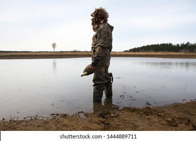 waterfowler with a duck decoy in his hand is on the shallow water