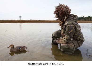 waterfowler with a plastic duck decoy in shallow water before the hunt